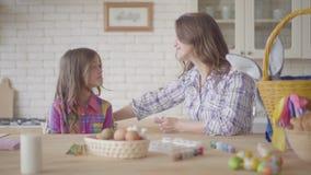 Mom και κόρη που κουβεντιάζουν καθμένος στον πίνακα Πάσχας με ένα καλάθ φιλμ μικρού μήκους