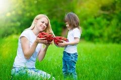 Mom και κόρη, που κρατούν τη φράουλα, διασκέδαση Στοκ Εικόνα