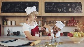 Mom και κόρη σε μια άνετη κουζίνα Μια μικρή κόρη χύνει το γάλα σε ένα ποτήρι Έννοια του προγεύματος, μαγείρεμα απόθεμα βίντεο