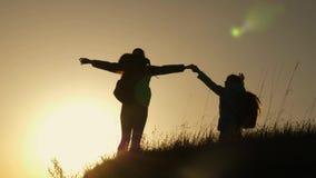 Mom και κόρη στις διακοπές που ταξιδεύουν και που χορεύουν στο βουνό Γυναίκα με τα αυξημένα χέρια πάνω από το βουνό που εξετάζει απόθεμα βίντεο
