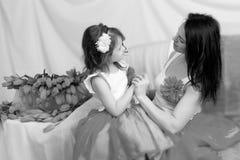 Mom και κόρη στον καναπέ με μια ανθοδέσμη των λουλουδιών Στοκ Φωτογραφίες