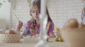 Mom και μικρό κορίτσι που χρωματίζουν τα αυγά Πάσχας με τα χρώματα και τη βούρτσα Προετοιμασία για τις διακοπές Πάσχας Μια ευτυχή απόθεμα βίντεο