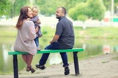 Mom και νέοι κόρη και μπαμπάς που περπατούν στο θερινό πάρκο Στοκ Εικόνα