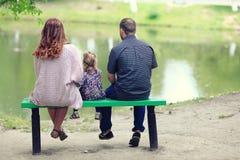 Mom και νέοι κόρη και μπαμπάς που περπατούν στο θερινό πάρκο Στοκ Φωτογραφία