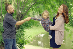 Mom και νέοι κόρη και μπαμπάς που περπατούν στο θερινό πάρκο Στοκ Φωτογραφίες