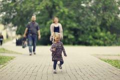 Mom και νέοι κόρη και μπαμπάς που περπατούν στο θερινό πάρκο Στοκ εικόνες με δικαίωμα ελεύθερης χρήσης