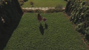 Mom και ο μικρός περίπατος κορών της στο πάρκο Πυροβοληθείς στον κηφήνα απόθεμα βίντεο