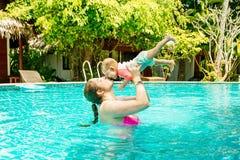 Mom με ένα ευτυχές μικρό παιδί οκτώ μηνών που έχουν τη διασκέδαση και που κολυμπούν στη λίμνη Νέα γυναίκα που φιλά το μωρό της στοκ φωτογραφία