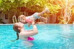 Mom με ένα μικρό παιδί οκτώ μηνών που έχουν τη διασκέδαση και που κολυμπούν στη λίμνη Θερινές διακοπές εν πλω Μια νέα γυναίκα κρα στοκ εικόνα με δικαίωμα ελεύθερης χρήσης