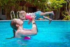 Mom με ένα μικρό παιδί οκτώ μηνών που έχουν τη διασκέδαση και που κολυμπούν στη λίμνη Θερινές διακοπές εν πλω Μια γυναίκα φιλά το στοκ εικόνες με δικαίωμα ελεύθερης χρήσης
