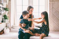Mom με τα παιδιά που τρώνε στον πίνακα κουζινών στοκ εικόνες