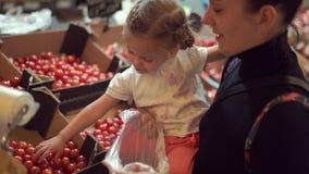 Mom με την λίγη κόρη στα όπλα της που επιλέγει τις ντομάτες σε μια υπεραγορά Αγοραστές στο κατάστημα απόθεμα βίντεο