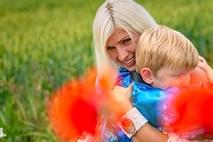 Mom με το γιο της σε ένα θαυμάσιο λιβάδι Το αγόρι αγκαλιάζει τη μητέρα του στενά και στοργικά στοκ εικόνες