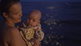 Mom με το μωρό στην παραλία τη νύχτα απόθεμα βίντεο