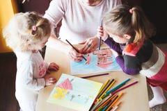 Mom με το σχεδιασμό μικρών κοριτσιών ζωηρόχρωμες εικόνες που χρησιμοποιούν το μολύβι γ Στοκ Εικόνες