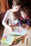 Mom με το σχεδιασμό μικρών κοριτσιών ζωηρόχρωμες εικόνες που χρησιμοποιούν το μολύβι γ Στοκ φωτογραφίες με δικαίωμα ελεύθερης χρήσης