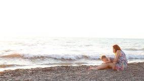 Mom με δύο αγόρια που κάθονται σε μια παραλία με τη θάλασσα γιων στο ηλιοβασίλεμα απόθεμα βίντεο