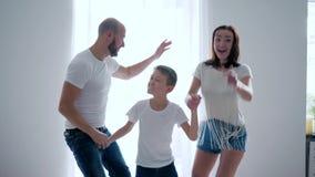 Mom, μπαμπάς και γιος στην ίδια άσπρη διασκέδαση μπλουζών μαζί που πηδά στο κρεβάτι, ευτυχείς στιγμές απόθεμα βίντεο