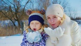 Mom που έχει τη διασκέδαση με την κόρη της 5 έτη Χαρείτε την καλή χειμερινή ημέρα, βγάλτε από τη θέση που ήταν το χιόνι από τα χέ απόθεμα βίντεο