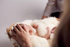 Mom που βάζει το μωρό στον ύπνο νεογέννητες δύο εβδομάδες Η έννοια της παιδικής ηλικίας Στοκ φωτογραφία με δικαίωμα ελεύθερης χρήσης