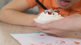 Mom που δίνει στο μικρό κορίτσι το νόστιμο κέικ κρέμας, κόρη που δαγκώνει το πρόχειρο φαγητό χρωματίζοντας απόθεμα βίντεο