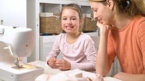 Mom που διδάσκει της λίγη κόρη για να ράψει τη χρησιμοποίηση της βελόνας φιλμ μικρού μήκους