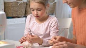 Mom που διδάσκει της λίγη κόρη για να ράψει τη χρησιμοποίηση της βελόνας απόθεμα βίντεο