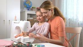 Mom που διδάσκει της λίγη κόρη για να ράψει να χρησιμοποιήσει μια ράβοντ φιλμ μικρού μήκους