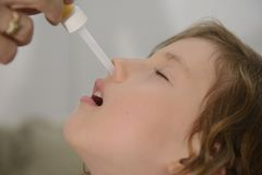 Mom που εφαρμόζει τις πτώσεις μύτης Στοκ εικόνες με δικαίωμα ελεύθερης χρήσης