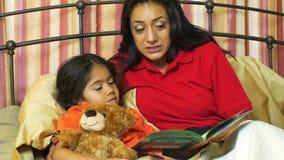 Mom που διαβάζει ένα βιβλίο στη νέα κόρη της απόθεμα βίντεο