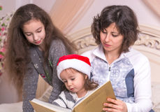 Mom που διαβάζει μια ιστορία Χριστουγέννων με τα παιδιά στοκ φωτογραφία