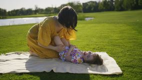 Mom που κάνει το γέλιο κορών μικρών κοριτσιών στο πάρκο απόθεμα βίντεο