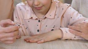 Mom που χρωματίζει προσεκτικά τα καρφιά κορών, που διδάσκουν τα καλλυντικά χρήσης, σαλόνι ομορφιάς απόθεμα βίντεο
