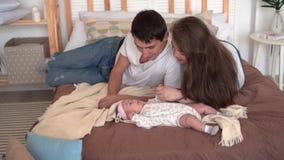 Χαμογελώντας οικογένεια στο κρεβάτι όπου ο μπαμπάς και mom προσέχει, αγγίζει και μιλά με την κόρη μωρών τους φιλμ μικρού μήκους