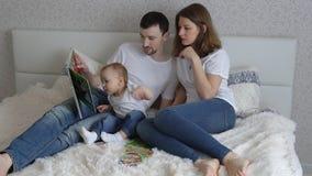 Νέο οικογενειακό παιχνίδι στο κρεβάτι στο σπίτι Παιχνίδι Mom και μπαμπάδων με την κόρη τους απόθεμα βίντεο