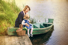Mom and adorable small daughter playing together in old wooden b Stock Photos