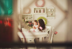 Mom And Baby Sits In The Kitchen Stock Photography