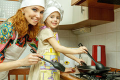 Mom And Daughter In White Chef Hats Cook In The Kitchen. Stock Photo