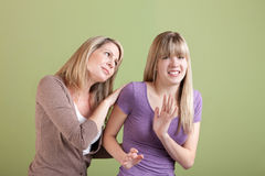 Mom and Annoyed Teen. Caucasian mom with annoyed daughter over green background Stock Images