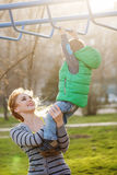 Mom assists son to the horizontal bars. Stock Photography