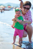 Mom and baby on beach  have fun Stock Photos