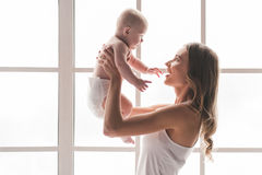 Mom and baby. Beautiful young mom is playing with her cute baby and smiling while standing near the window at home royalty free stock photos