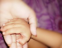 Mom and baby bond hand on hand it is trust. stock photo