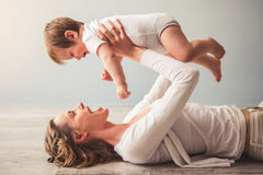Mom and baby boy. Beautiful mom is playing with her cute baby boy at home and smiling royalty free stock image