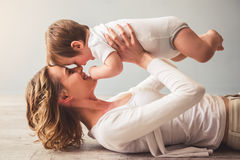 Mom and baby boy. Beautiful mom is playing with her cute baby boy at home and smiling stock images