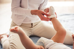 Mom and baby boy. Cropped image of beautiful mom putting on her cute baby socks Stock Photography