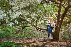 Mom with baby boy sitting on tree branch in the flowered spring garden Royalty Free Stock Photo