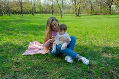 Mom with baby in bright clothes on a pink plaid on the green right. Family resting in the park on a warm day stock images