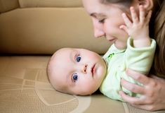 Mom and baby. Cuddling on the couch Royalty Free Stock Image