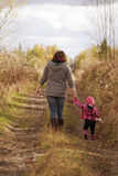 Mom and Baby Daughter with Teddy Walking on Gravel Royalty Free Stock Photo